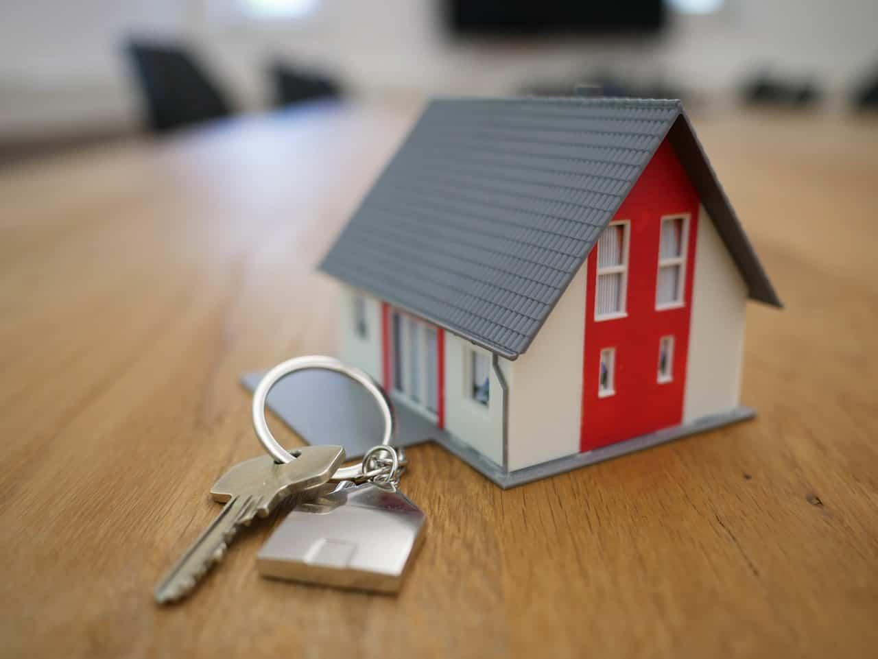 מודל בית משפחתי על שולחן ולידו מפתחות לבית